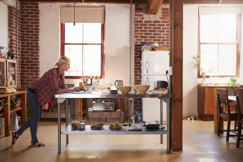 Молодая женщина используя компьютер в кухне, полнометражном взгляде со стороны стоковые фото