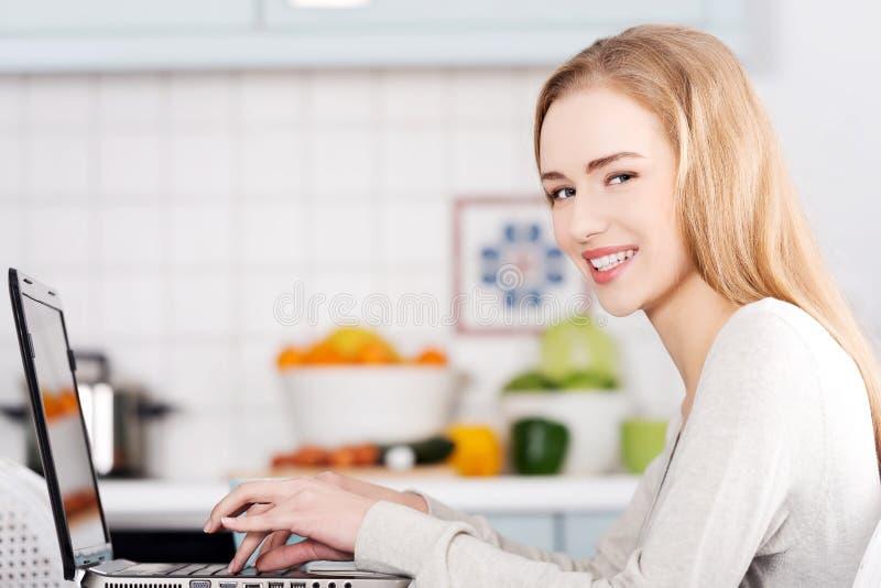 Молодая женщина используя портативный компьютер дома стоковое фото rf