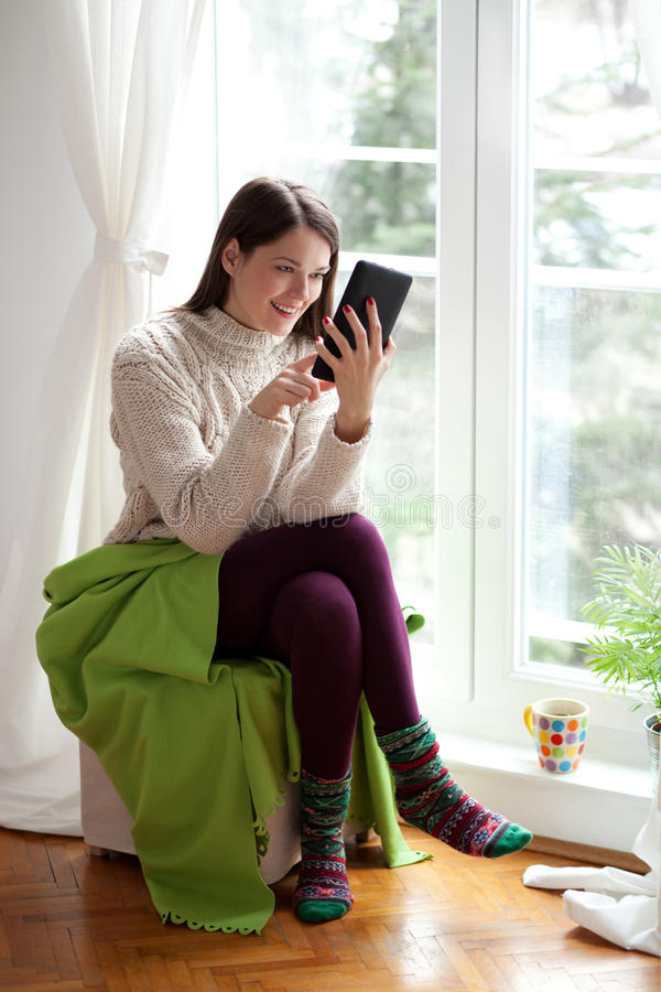 Молодая женщина используя таблетку стоковые фото