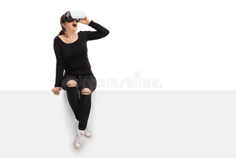 Молодая женщина используя шлемофон виртуальной реальности и сидящ на панели стоковое изображение rf