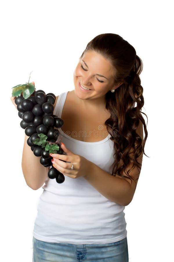 Молодая женщина и виноградины на белизне стоковая фотография