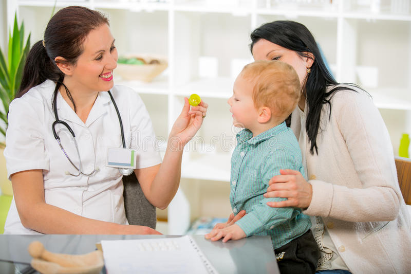 Молодая женщина и ее ребенок на homeopaths доктора стоковые изображения
