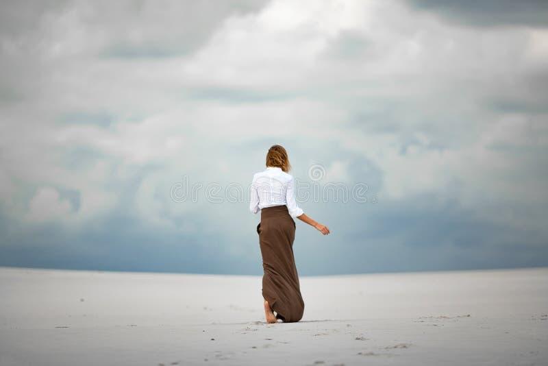 Молодая женщина идет barefoot в пустыню задний взгляд стоковое изображение rf