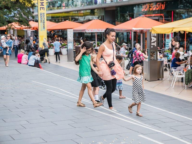 Молодая женщина и несколько детей идут за Southbank Centr стоковое изображение rf