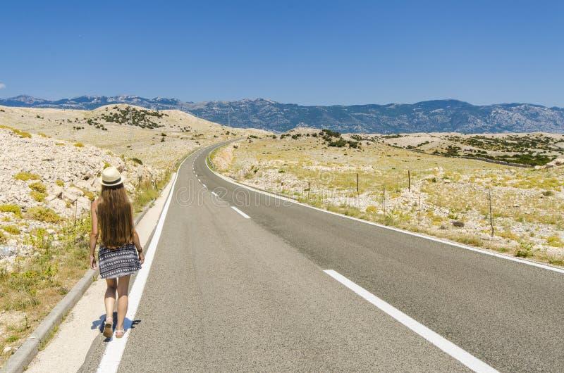 Молодая женщина идя вдоль пустой дороги стоковые изображения rf