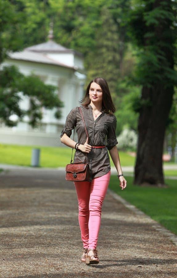 Молодая женщина идя в парк стоковые изображения rf