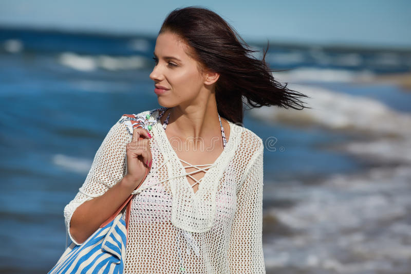 Молодая женщина идя в платье пляжа воды нося белое стоковое фото