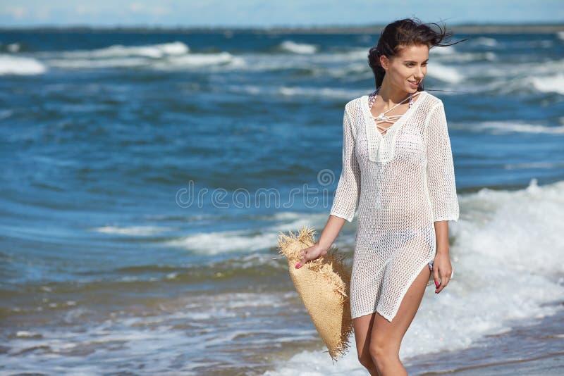 Молодая женщина идя в платье пляжа воды нося белое стоковая фотография rf