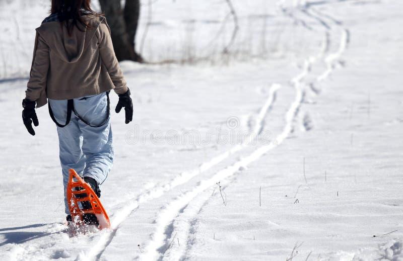 Молодая женщина идя с 2 оранжевыми snowshoes в горах в wi стоковое изображение