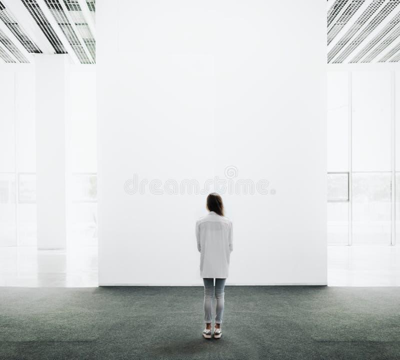 Молодая женщина идя через галерею и смотреть стоковые изображения rf
