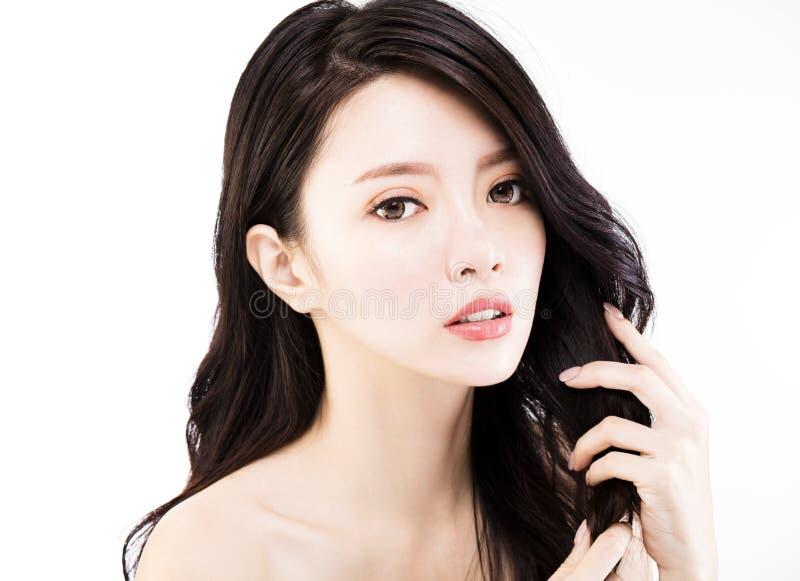 Молодая женщина касаясь ее здоровым черным волосам стоковая фотография