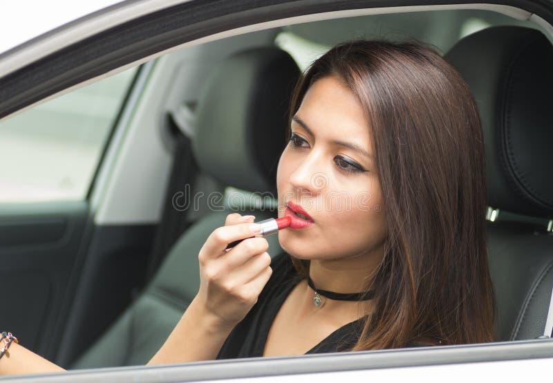 Молодая женщина крупного плана сидя в автомобиле кладя на состав смотря в зеркало, как увидено от внешней стороны окна водителей, стоковые фотографии rf