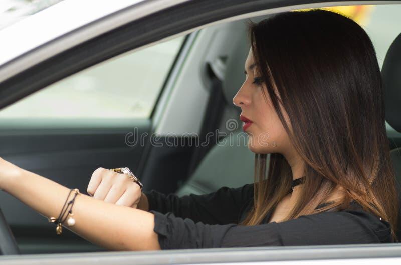 Молодая женщина крупного плана сидя в автомобиле смотря наручные часы, как увидено от внешней стороны окна водителей, женская кон стоковая фотография rf