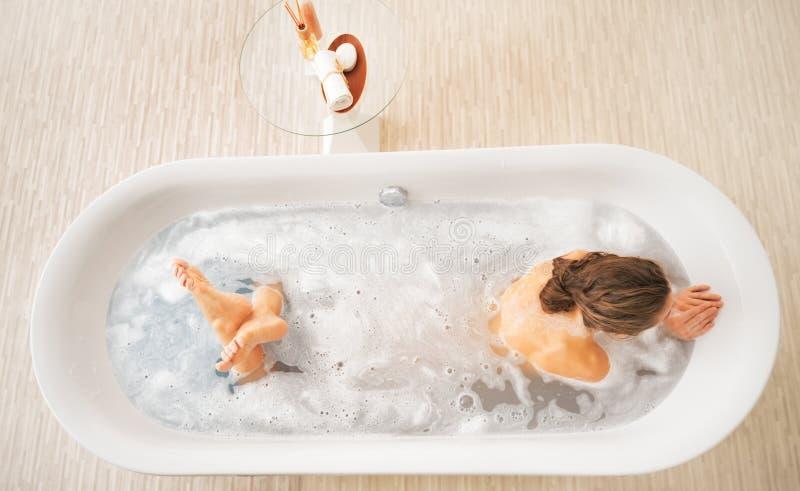 Молодая женщина кладя в ванну стоковое изображение