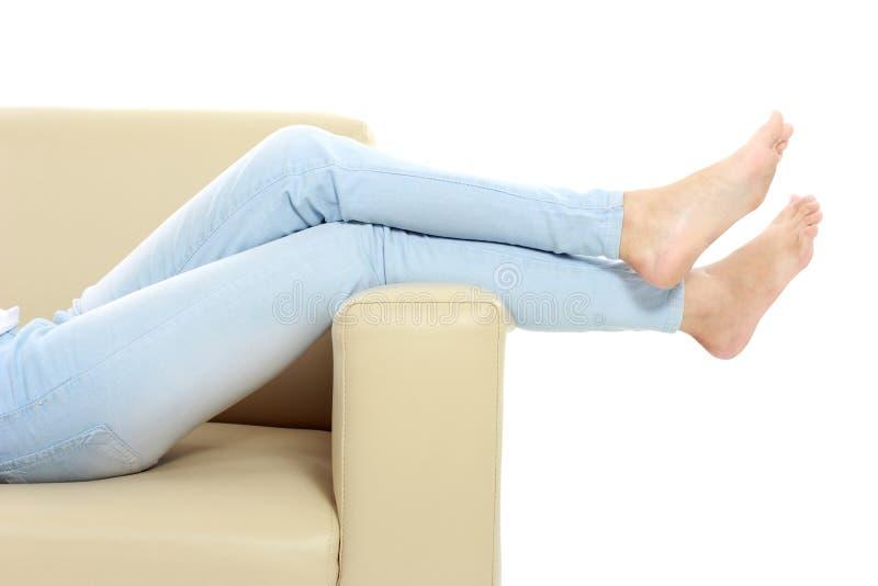 Молодая женщина кладя ее ноги вверх стоковая фотография