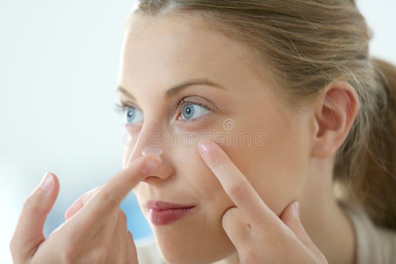 Молодая женщина кладя линзы окуляра стоковое изображение