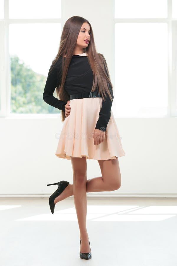 Молодая женщина моды стоит на одной ноге стоковое изображение