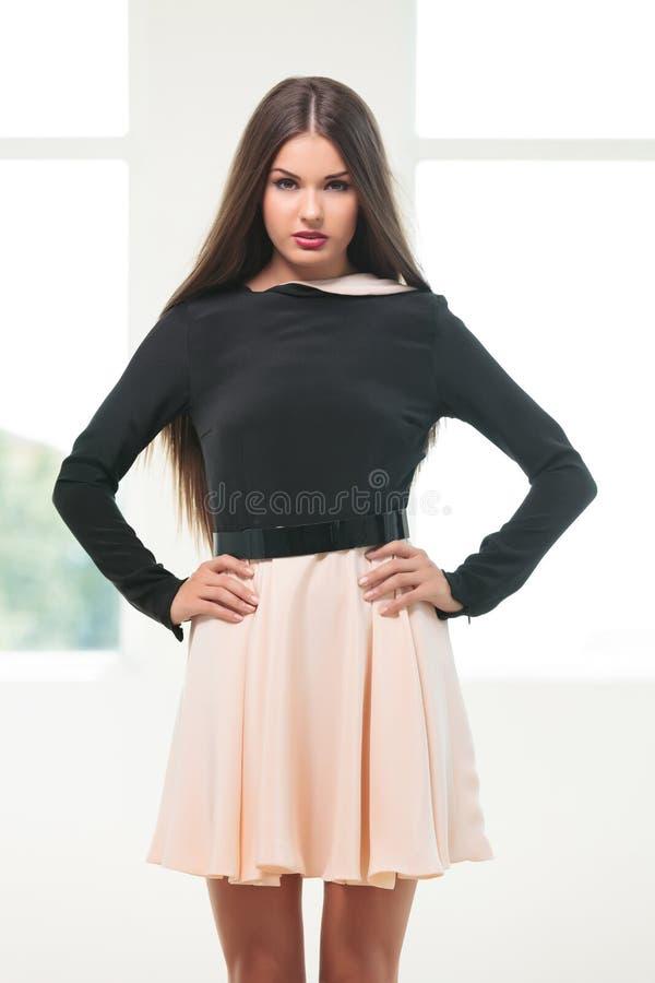 Молодая женщина моды с руками на бедрах стоковая фотография