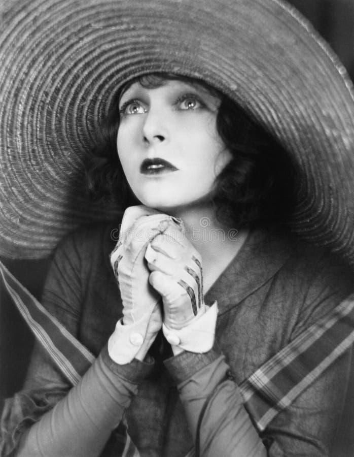 Молодая женщина моля в большой шляпе (все показанные люди более длинные живущие и никакое имущество не существует Гарантии постав стоковое фото