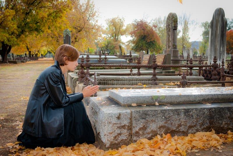 Молодая женщина моля на могиле в кладбище в падении стоковая фотография