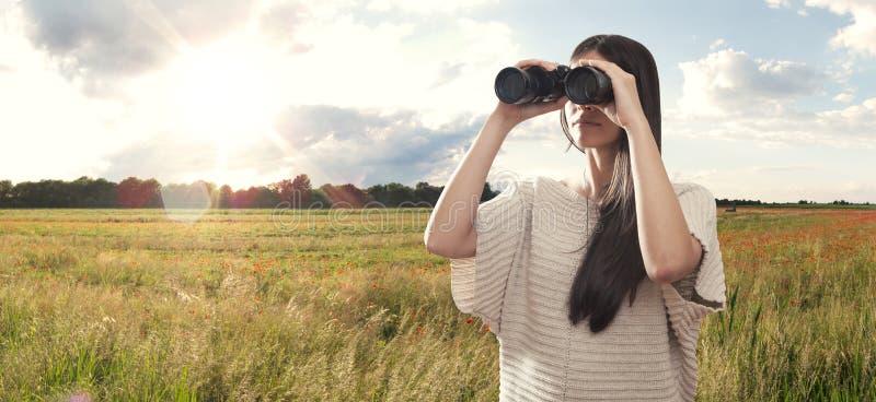 Молодая женщина наблюдая с бинокулярным стоковые изображения rf