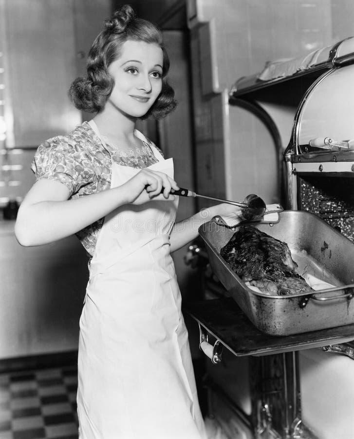 Молодая женщина наметывая гусыню в кухне (все показанные люди более длинные живущие и никакое имущество не существует Гарантии по стоковое фото rf