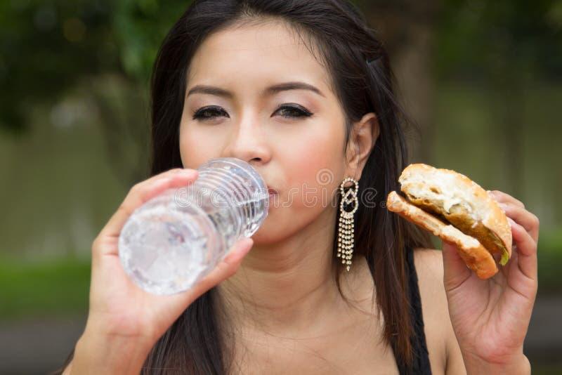Молодая женщина наслаждаясь бургером цыпленка стоковые фотографии rf