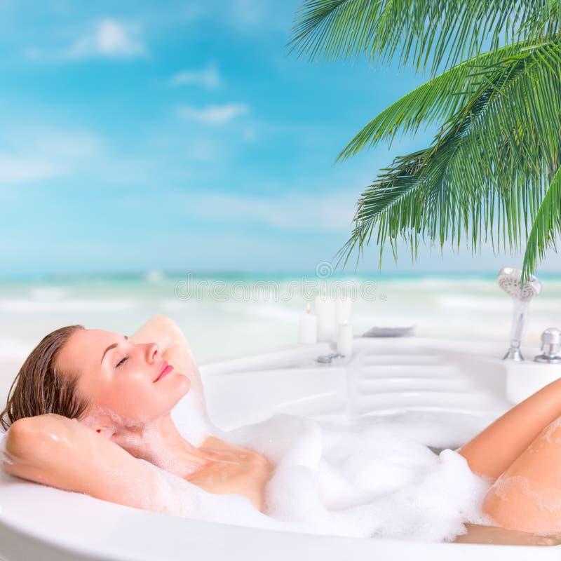 Молодая женщина наслаждаясь ванной в курорте стоковая фотография rf