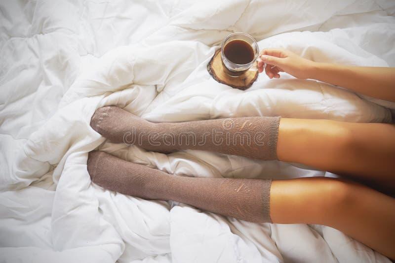 Молодая женщина наслаждаясь ее кофе пока сидящ в кровати стоковая фотография rf