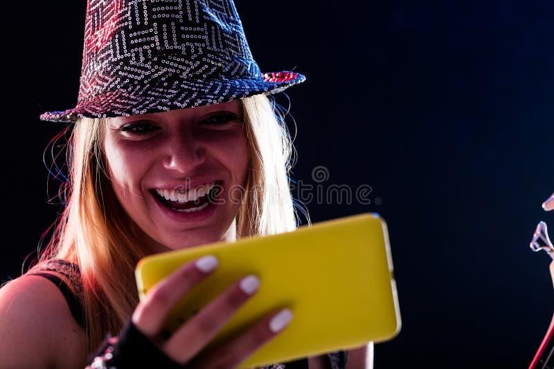 Молодая женщина наслаждаясь живым развлечением онлайн стоковое фото