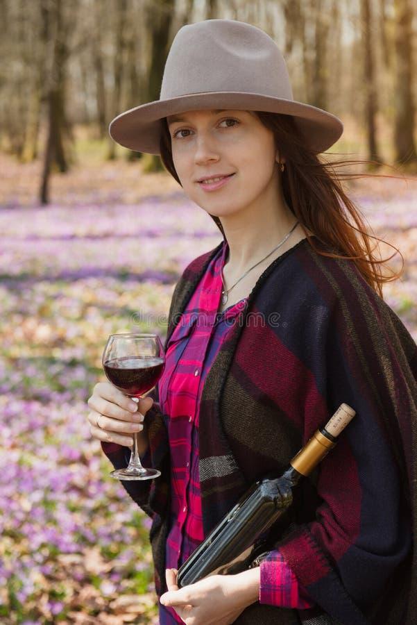 Молодая женщина наслаждаясь красным вином outdoors стоковое фото