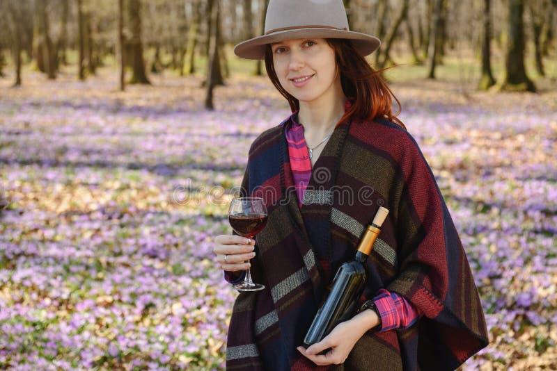 Молодая женщина наслаждаясь красным вином outdoors стоковые изображения