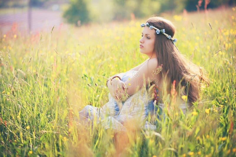Молодая женщина наслаждаясь погодой весны в поле цветка стоковые изображения rf