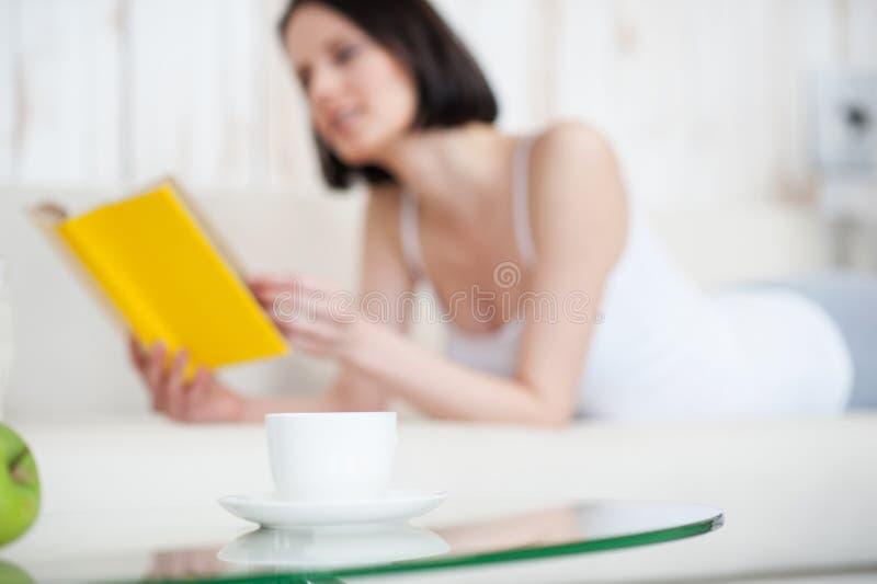 Молодая женщина наслаждаясь хорошей книгой стоковая фотография rf