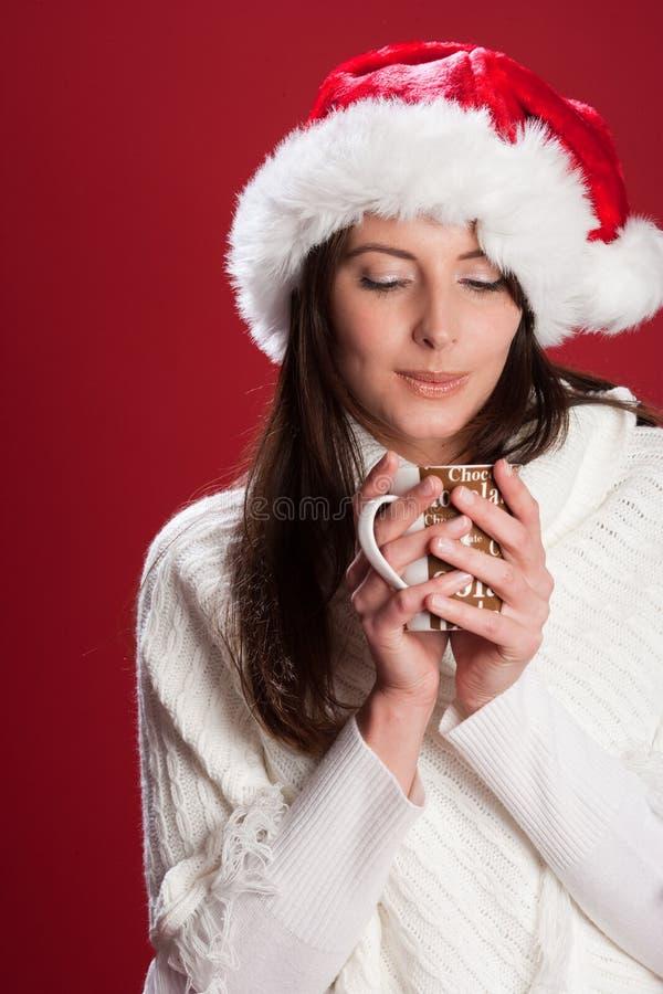 Молодая женщина наслаждаясь чашкой горячего шоколада стоковые изображения