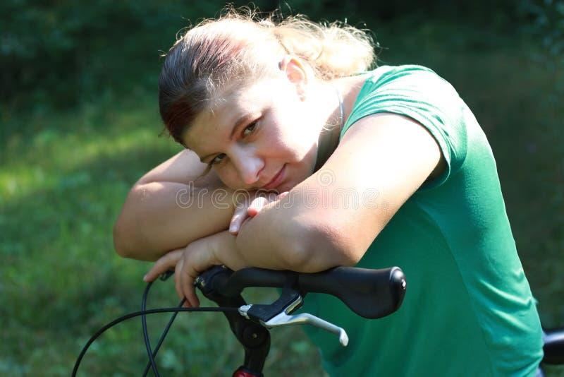 Молодая женщина на велосипеде стоя на дороге и смотря к где-то стоковые фотографии rf