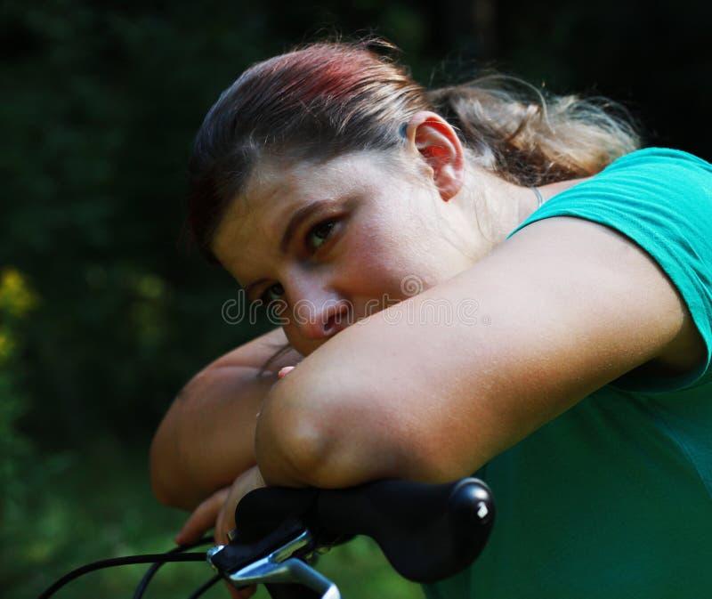 Молодая женщина на велосипеде стоя на дороге и смотря к где-то стоковое фото rf
