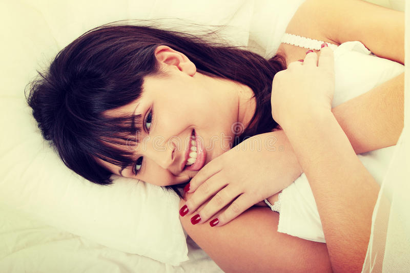 Молодая женщина на кровати стоковые изображения