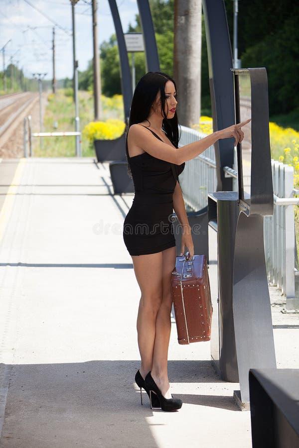 Молодая женщина на платформе вокзала ищет informat стоковые изображения