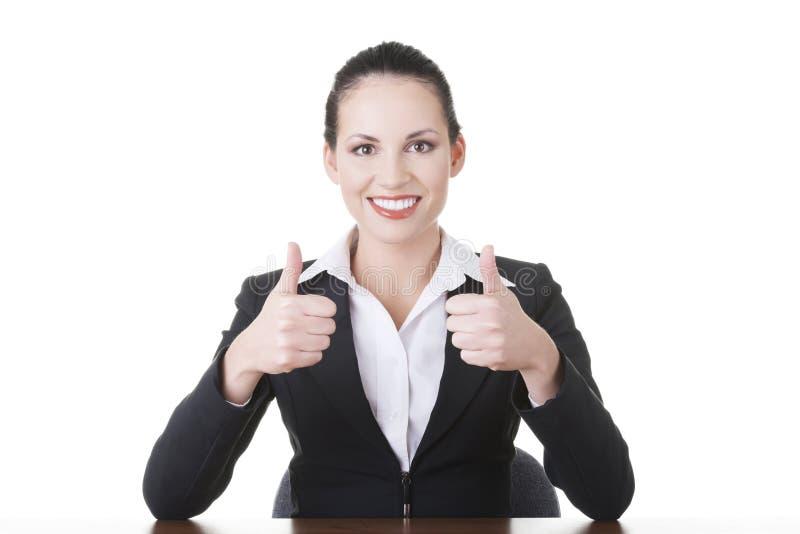 Молодая женщина на столе gesturing О'КЕЫ стоковые изображения