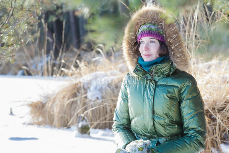 Молодая женщина нося зеленую с капюшоном реальную отделку меха вниз покрывает наслаждаться взглядом в лесе зимы outdoors стоковое фото