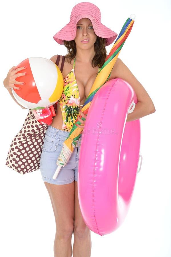 Молодая женщина нося костюм заплыва на празднике нося шарик пляжа стоковое фото rf