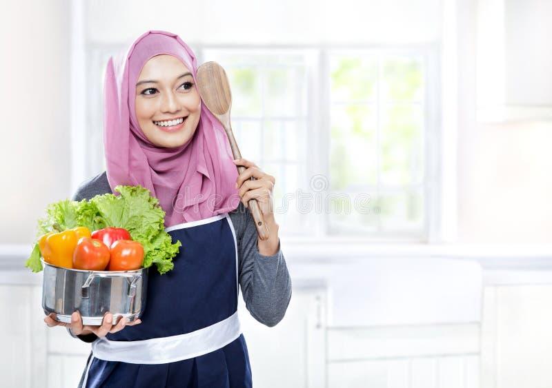 Молодая женщина нося лоток вполне овощей и деревянного шпателя стоковые изображения rf