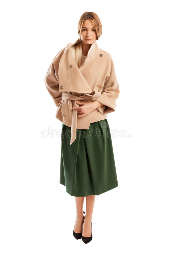 Молодая женщина нося пальто светлого цвета и зеленую юбку стоковое фото