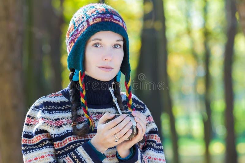 Молодая женщина нося связанную шерстистую шляпу и держа горячее питье ответной части yerba стоковая фотография rf