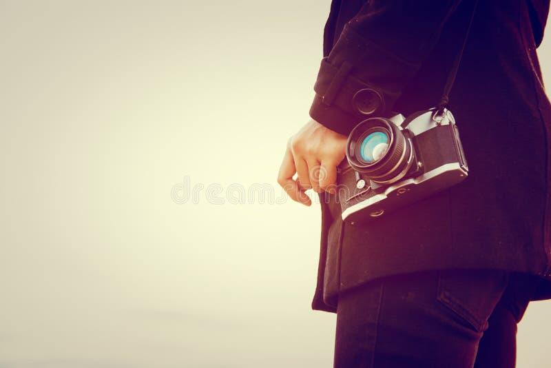 Молодая женщина нося черное положение пальто носит ретро камеру стоковое изображение
