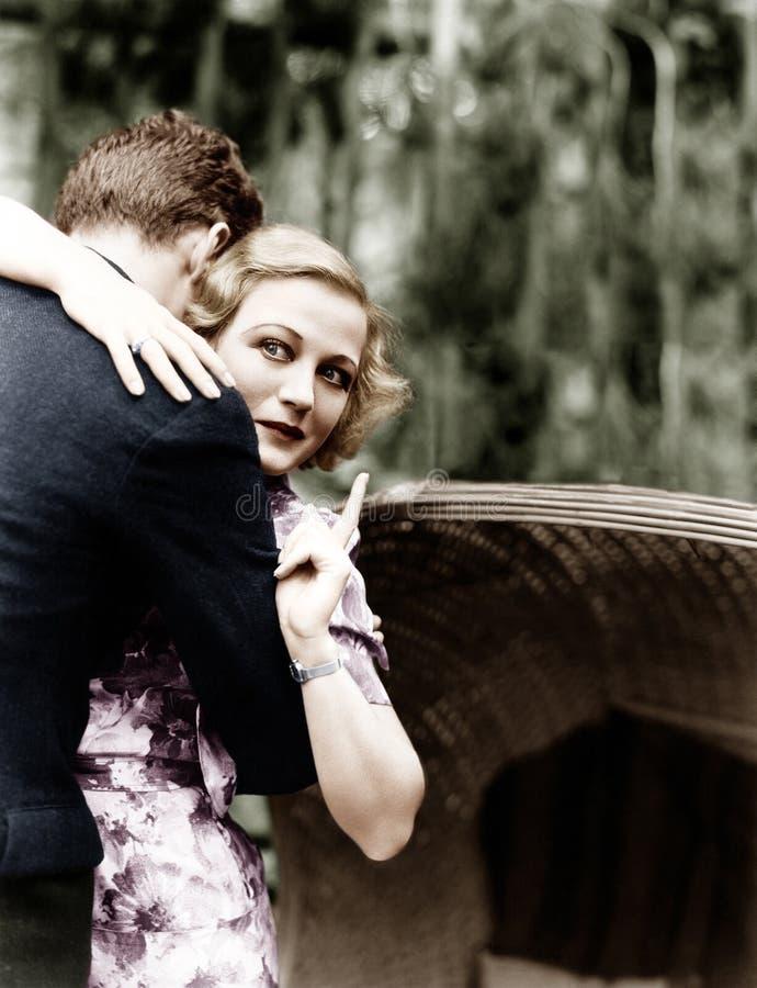 Молодая женщина обнимая человека и указывая к доске информации (все показанные люди нет более длинные живущих и никакого имуществ стоковые фото