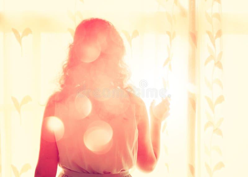 Молодая женщина около окна ждать кто-то стоковое фото rf