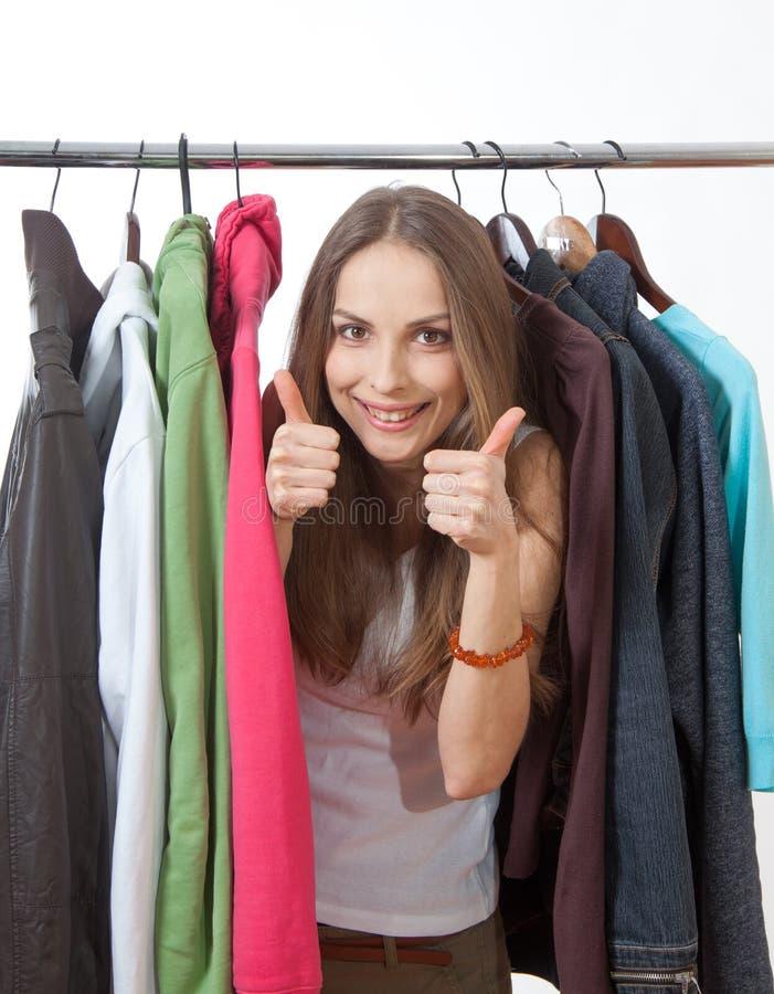Молодая женщина около шкафа с вешалками стоковые изображения rf