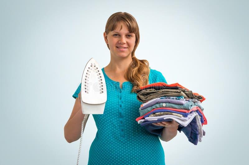 Молодая женщина домохозяйки с кучей одежд стоковые изображения